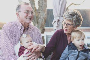 grandparents holding toddler grandchildren