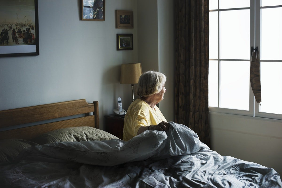 lady sitting on bed looking out window