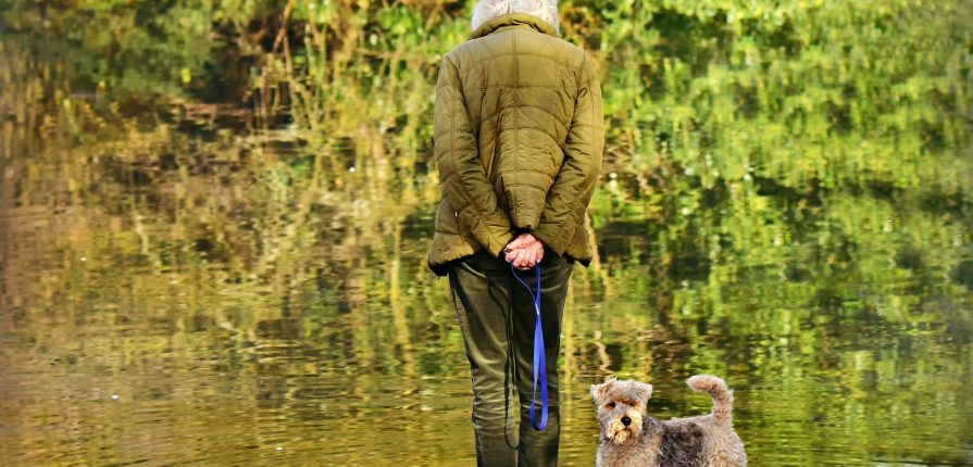 elderly woman standing on a river bank with her dog