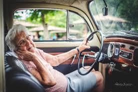 elderly woman holding steering wheel